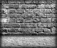 Grungy textured brick and stone wall with cracked ground Stock Images