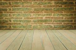 Grungy texturerad röd tegelsten och stenvägg med eftersatta för varm brun trägolvinsida den gamla och öde inre, murverket och kar Royaltyfri Fotografi