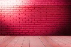 Grungy texturerad röd tegelsten och stenvägg med eftersatta för varm brun trägolvinsida den gamla och öde inre, murverket och kar Fotografering för Bildbyråer