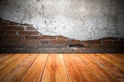 Grungy texturerad röd tegelsten och stenvägg med eftersatta för varm brun trägolvinsida den gamla och öde inre, murverket och kar Royaltyfri Bild