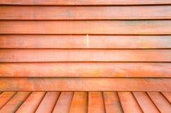 Grungy texturerad röd tegelsten och stenvägg med eftersatta för varm brun trägolvinsida den gamla och öde inre, murverket och kar Royaltyfria Foton