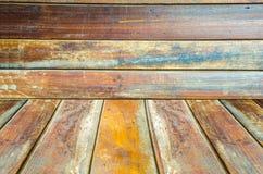 Grungy texturerad röd tegelsten och stenvägg med eftersatta för varm brun trägolvinsida den gamla och öde inre, murverket och kar Arkivbild