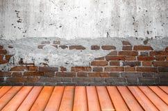 Grungy texturerad röd tegelsten och stenvägg med eftersatta för varm brun trägolvinsida den gamla och öde inre, murverket och kar Royaltyfri Foto