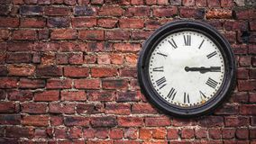 Grungy time lapse station clock. A time-lapse of a grungy retro station clock moving through 24 hours against a red brick wall with copy space royalty free illustration