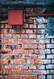 Grungy urban background of a brick wall with electric box Stock Images
