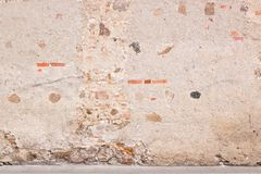 Old weathered vintage brick wall with broken plaster and pavement on the ground. Grungy urban background. stock images