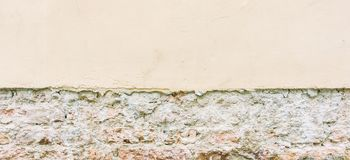 Old weathered vintage brick wall with broken plaster and pavement. Grungy urban background. stock image