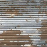 Grungy industrial brown metal door with peeling white paint Royalty Free Stock Photography