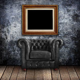 Grungy wall with Classic Brown leather armchair and gold frames Stock Images