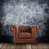Grungy wall with Classic Brown leather armchair and old wood. Background Royalty Free Stock Image