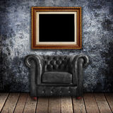 Grungy wall with Classic Brown leather armchair and old wood Stock Photos