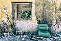 Shabby green sofa on a worn yellow wall royalty free stock images