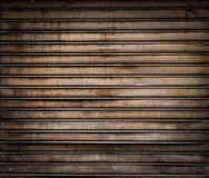Grungy weathered metallic roll up door. Rusty iron gate. Stock Photos