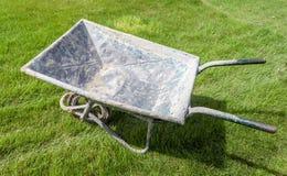 Grungy wheelbarrow on green grass in the garden Royalty Free Stock Photo