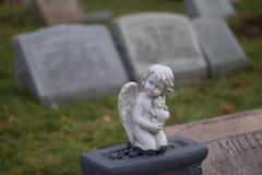 Grunt djup för yttre dag av fältmaterielfotoet av ängeln på gravstenen i monteringshoppkyrkogård Arkivfoton