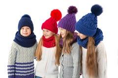 Grupa śliczni dzieciaki w zima ciepłych kapeluszach szalikach na bielu i Dziecko zima odziewa Fotografia Royalty Free