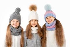 Grupa śliczni dzieciaki w zima ciepłych kapeluszach szalikach na bielu i Dziecko zima odziewa Obrazy Royalty Free