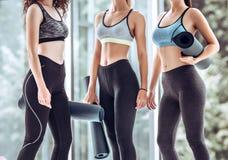 Grupa żeńscy przyjaciele ono uśmiecha się wpólnie w sportswear podczas gdy stojący w gym po joga treningu obraz stock