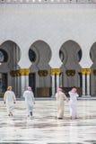 Grupa arabscy mężczyzna chodzi w kierunku meczetu brać na Kwietniu 01, 2013 w Abu Dhabi, Zlany Arabski emirat obraz royalty free
