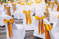 Grupa biała spandex krzeseł pokrywa z złocistą organza szarfą dla plażowego ślubu miejsca wydarzenia przygotowania fotografia stock