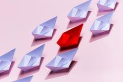 Grupa białego papieru statek w jeden kierunku i jeden czerwieni papierowym shi fotografia stock