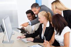 Grupa biznesmeni patrzeje komputer Zdjęcia Royalty Free