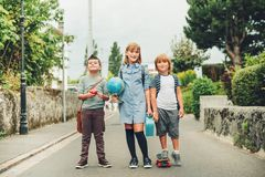 Grupa chodzi z powrotem szkoła trzy śmiesznego dzieciaka jest ubranym plecaki Obraz Stock