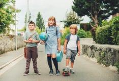 Grupa chodzi z powrotem szkoła trzy śmiesznego dzieciaka jest ubranym plecaki Fotografia Stock