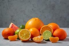 Grupa cytrus owoc - tangerines, cytryny, wapno, pomara?cze, grapefruits na powierzchni szaro?? st?? przeciw szaro?ci fotografia stock