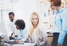 Grupa cztery coworkers dyskutuje plany biznesowych w nowożytnym biurze Młodzi ludzie robi doskonałym pomysłom Horyzontalny, zamaz zdjęcie royalty free