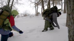 Grupa cztery przyjaciela wycieczkuje w zimie wpólnie z dużymi plecakami, drużyna iść ciężki zdjęcie wideo