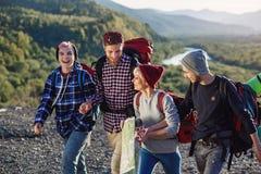 Grupa cztery szczęśliwego podróżnika chodzi z mapą i próbuje znajdować za prawym sposobie na góra wierzchołku przy zmierzchem obraz royalty free
