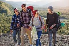 Grupa cztery szczęśliwego podróżnika chodzi z mapą i próbuje znajdować za prawym sposobie na góra wierzchołku przy zmierzchem fotografia stock