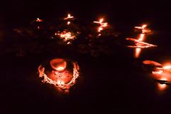 Grupa dekorująca Diya Nafciana lampa zaświecał w festiwalu sezonie Diwali na czarnym tle Pojęcie usuwać ciemność fotografia royalty free