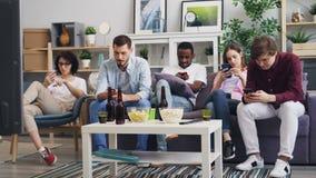 Grupa dotyka ekran w domu młodzi ludzie używa smartphones wpólnie zbiory wideo