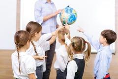 Grupa dzieci i nauczyciel trzyma kulę ziemską zdjęcie stock