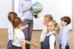 Grupa dzieci i nauczyciel trzyma kulę ziemską fotografia stock