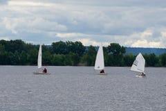 Grupa dzieci na żeglowanie łodziach współzawodniczy w regatta przy morzem zdjęcia royalty free