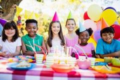Grupa dzieci ono uśmiecha się i pozuje podczas przyjęcia urodzinowego Fotografia Royalty Free