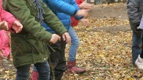 Grupa dzieci rzuca żółtego jesieni ulistnienie up zbiory wideo