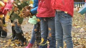 Grupa dzieci rzuca żółtego jesieni ulistnienie up zbiory