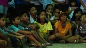 Grupa dzieci siedzi na cegiełki podłoga podczas gdy oglądający rockowego tana konkurs podczas grodzkiego uczty społeczeństwa wyda zbiory