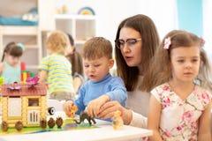Grupa dzieciaki bawić się z nauczycielem w dziecinu obraz royalty free