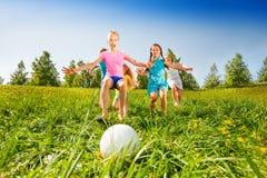 Grupa dzieciaki biega piłka w łące Fotografia Stock