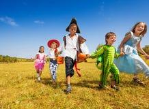 Grupa dzieciaki biega w parku z kostiumami Fotografia Stock