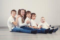 Grupa dzieciaki siedzi na podłoga w cajgach Fotografia Royalty Free