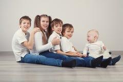 Grupa dzieciaki siedzi na podłoga w cajgach Fotografia Stock