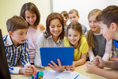 Grupa dzieciaki z nauczyciela i pastylki komputerem osobistym przy szkołą Fotografia Stock