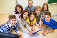Grupa dzieciaki z nauczyciela i pastylki komputerem osobistym przy szkołą obrazy stock