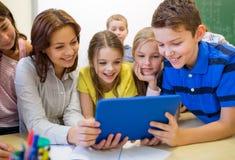 Grupa dzieciaki z nauczyciela i pastylki komputerem osobistym przy szkołą Zdjęcie Royalty Free